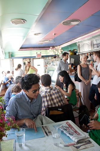 happyish assortment of people in many pastel Diner