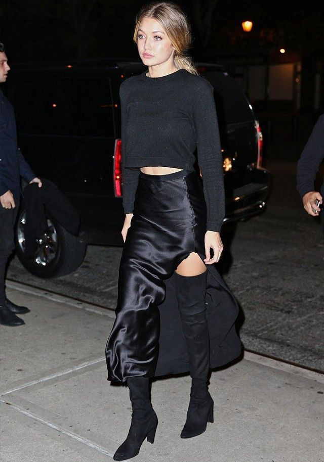 Gigi Hadid wears a cashmere cropped sweater, silk high-slit skirt, and thigh-high suede boots