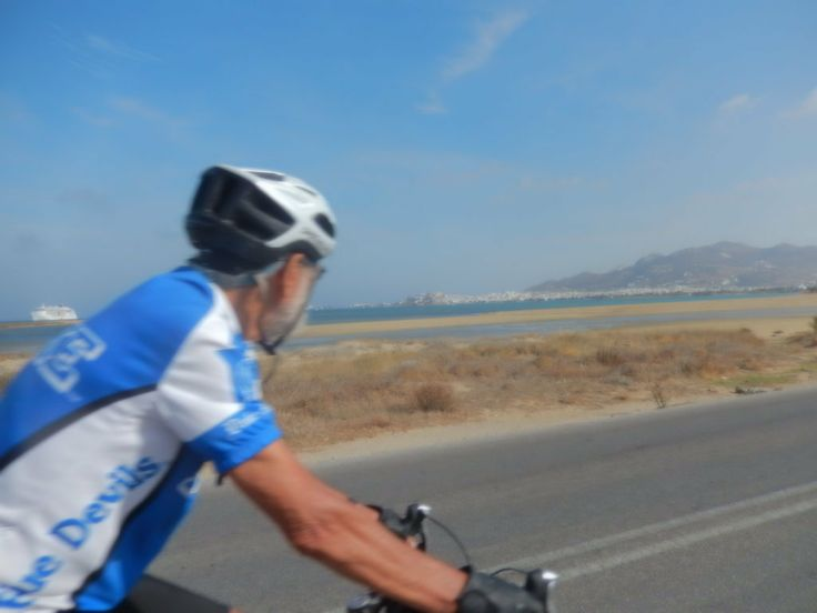 Peter from North Carolina, 85 years old and still pedaling strong, heads towards Chora on the flat sea coast road near the airport.