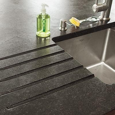 Grooves, cut next to the sink in this soapstone counter, act as a drainboard. | Photo: Deborah Whitlaw Llewellyn | thisoldhouse.com