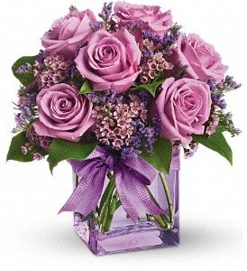 Lavender roses and waxflower, purple limonium and greens are hand-delivered in a lavender cube that's all wrapped up with a vibrant purple taffeta ribbon.