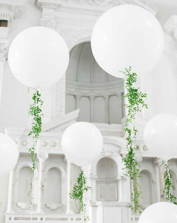 Floral wedding decorations and ideas. Inspirational wedding ideas with green plants. Balloons covered with plants.