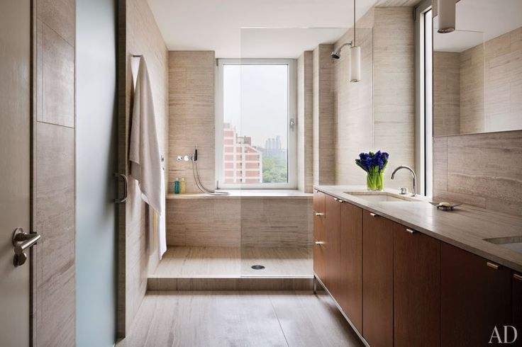 Sheathed in wood-grain marble, the master bath of a Manhattan penthouse by Steven Harris Architects features a vanity with cerused-oak doors.