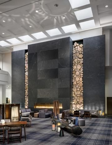 A ceiling high stone fireplace framed by rustic wooden for 8 design hotel