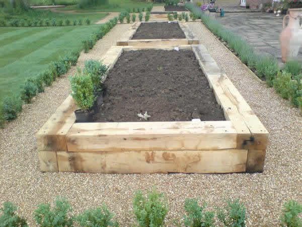 Oak railway sleepers used to create raised vegetable beds.