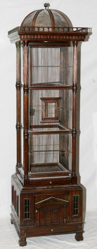 "MAITLAND SMITH, MAHOGANY BIRDCAGE, H 84"", W 24"", L 24"":fluted column corners, gallery with a bent glass dome at the top; narrow pull out waste tray below cage. Classical design on cabinet door at the bottom with miniature framed windows. Narrow storage drawer at very bottom with brass pull all supported on square feet."