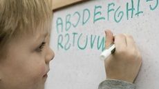 Close-up of a young child writing letters on a white board | Should I Be Worried About My Child Reversing Letters?