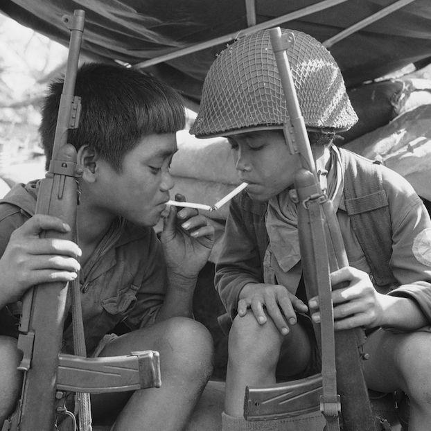 Due ragazzini soldato di 12 e 14 anni fumano dopo un aver pattugliato la zona circostante a Song De, in Vietnam, prima del sorgere del sole, 7 marzo 1969