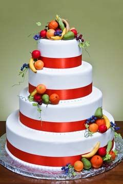 Classic four tier white wedding cake garnished with miniature handcrafted fruits; bananas, oranges, green pears and red apples. Decorated red ribbon around each tier. From www.jacquespastries.com   ........   #wedding #cake #birthday