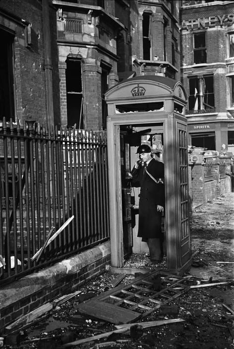 An Air-raid Warden phones from a shattered booth after a bombing raid in London, 1940 (George Rodger)
