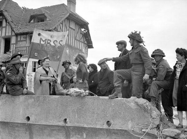 Infantrymen of Le Régiment de la Chaudière talking with French civilians, Bernières-sur-Mer, 6 June 1944. Sergeant Rosaire Gagnon (arm extended) de Quebec was killed a few days later, june 13 1944. Photographer: Frank L. Dubervill