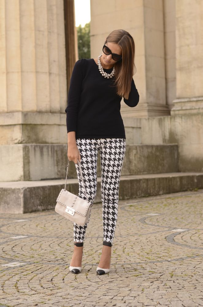Love houndstooth! Black top, white statement necklace, houndstooth patterned jeans and black shoes, white purse