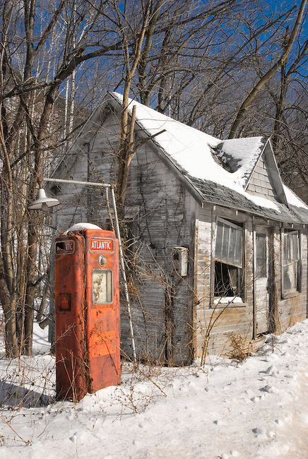 Gas station abandoned in winter snow and sunlight along the roadside, 1960's rustic Americana.