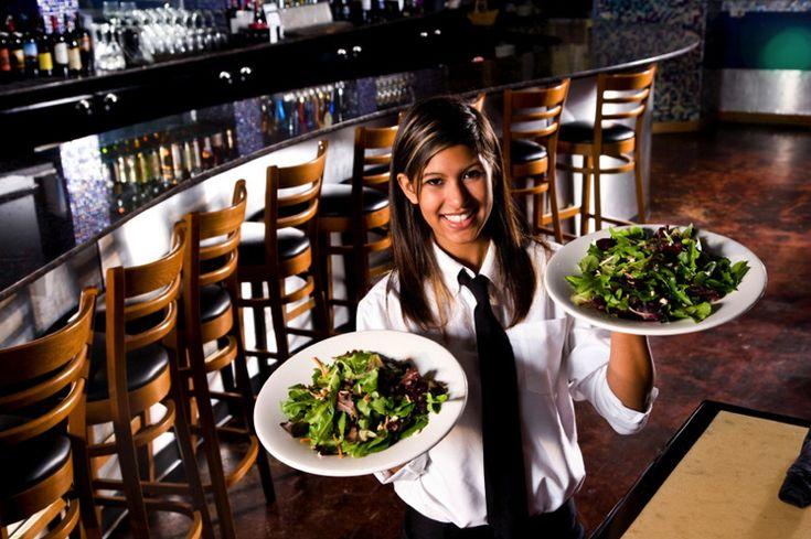 Smiling waitress serving salads