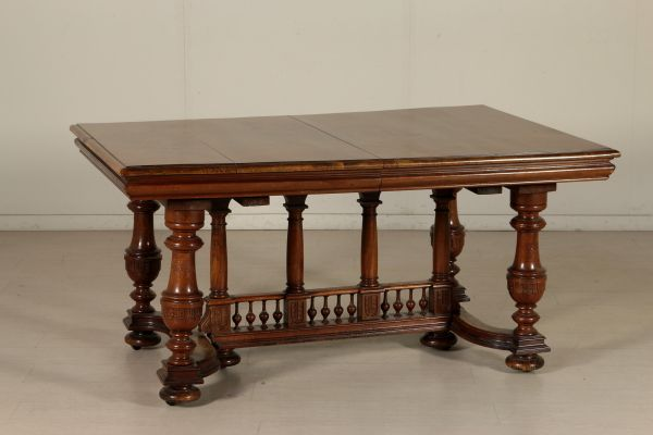 Tavolo allungabile in noce retto da gambe tornite e castello con colonnine in linea. Piano apribile. Basamento intagliato.