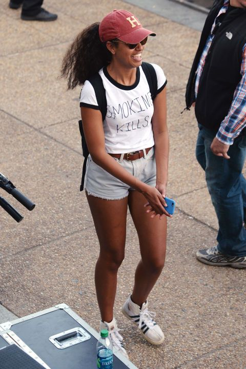"""After causing a frenzy when she was reportedly caughtsmoking weed at Lollapalooza, Malia Obama trolls her critics ina DIY t-shirt with """"Smoking Kills"""" written on the front while attending another music festival, Made in America, this weekend. She completed the casual look with K-Swiss sneakers, belted denim shorts, sunglasses and a baseball cap from Harvard, where she'll be attending in the fall."""