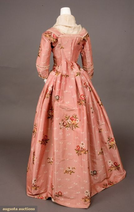 1770-1780 Sack back open gown of rose pink ribbed silk brocaded with scattered multicolored flower sprays and small cream flower sprigs, looped cream silk fringe trim, bodice with pendant self fabric bands to cross-over and pin under arms, center front eyelets forlacing, skirt knife pleated to bodice, interior linen waist tapes and loops for polonaise effect, homespun linen bodice and sleeve linings, hem deeply faced with soft cream China silk.