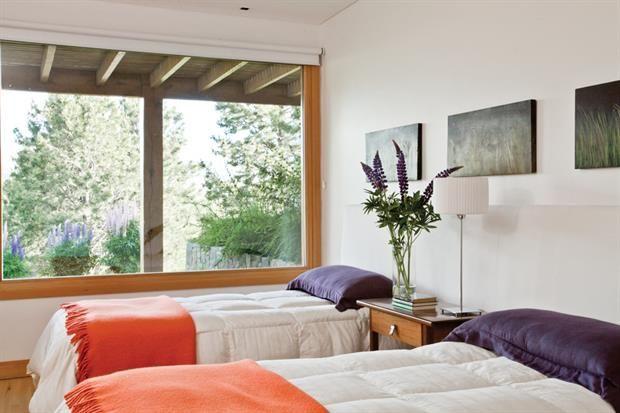 Deco moderna: dos casas con estilo actual  La decoración del dormitorio de huéspedes sigue con la línea minimalista del resto de la casa, pero acá almohadones y tapizados dan la nota de color, a tono con los lupinos de primavera..