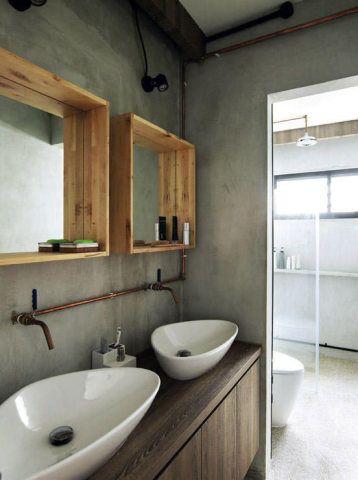 De estilo rústico, este banheiro possui cubas e espelhos duplos – os últimos receberam moldura de madeira que se assemelha à paletes. Destaque para os canos em cobre que dão forma às torneiras.