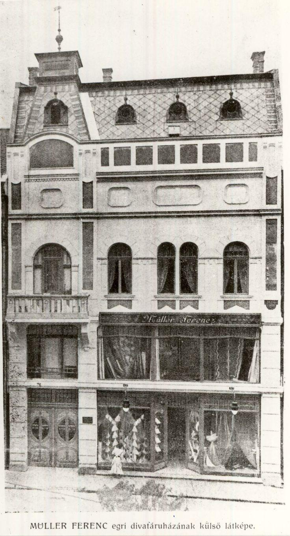 Müller Ferenc egri divatáruházának külső látképe 1911-ből. Az áruház az épület földszintjét és galériáját foglalja el. A kirakatban méteráru és divatáru látható.