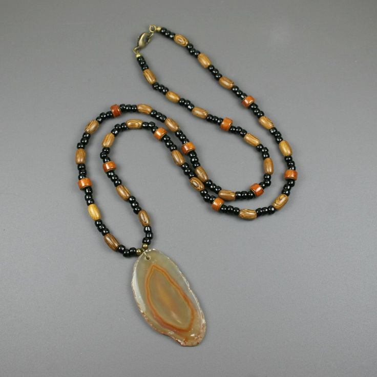 Agate slice pendant in amber colors on beaded strand of black glass seed beads, river stone, wood, and antiqued brass from the Earthwear Collection