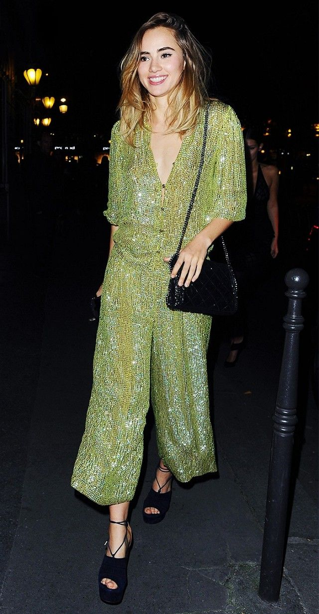 Suki Waterhouse wears a green sequin jumpsuit with a black shoulder bag and platforms