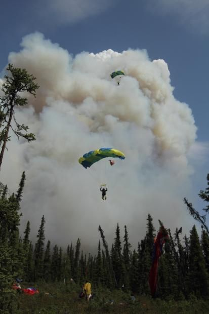 Hastings fire, 5-31, Mike McMillan,Two smokejumpers approaching landing zone in clearing with smoke column in background
