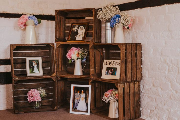 Displaying family wedding photos is a lovely touch showing two families coming together. Photo by Benjamin Stuart Photography #weddingphotography #familyphotos #ceremonydecor #familyhistory #woodencrates #weddingflowers