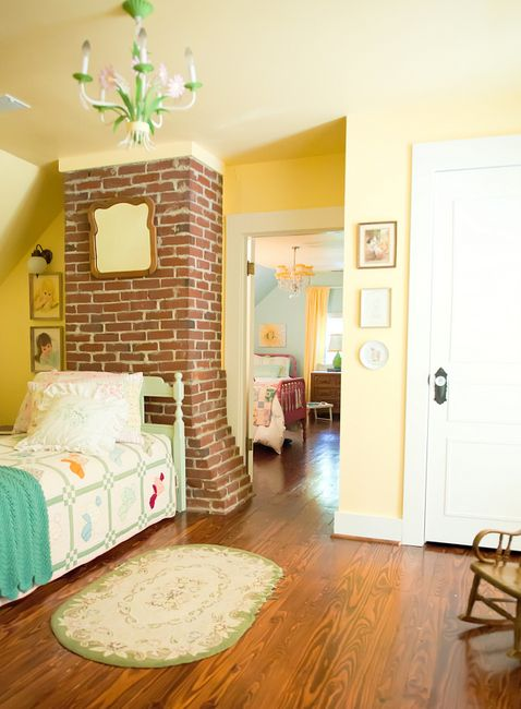 Benjamin Moore's Hawthorne Yellow with turquoise accents, and warm wood floors and brick. Love the fireplace