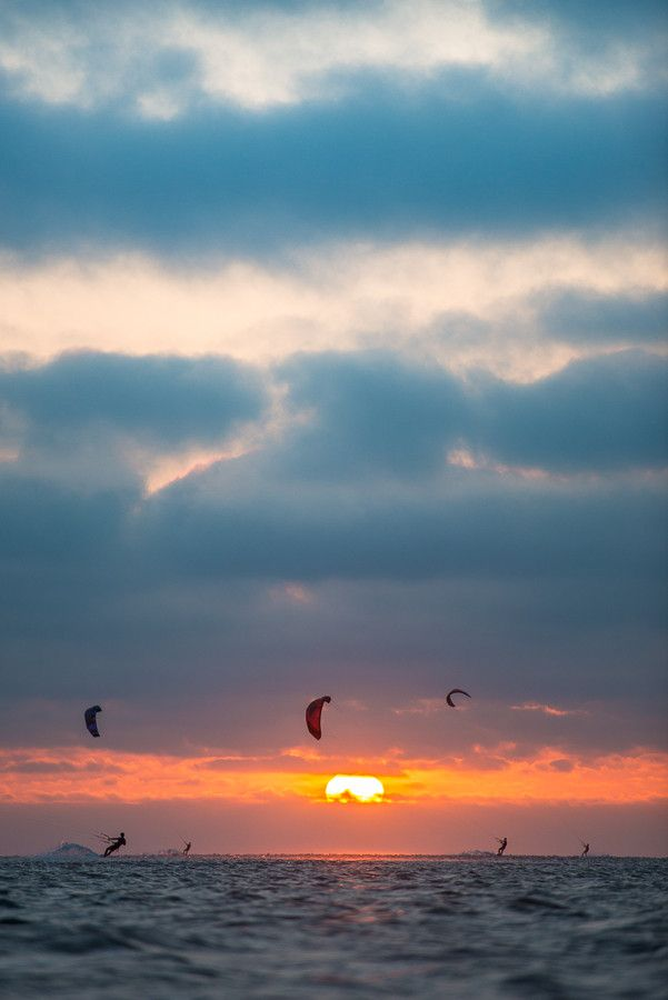 A group of outdoor athletes as seen kitesurfing on a sunny and windy evening at the North Sea, near the bay of Lauwersoog, the Netherlands.