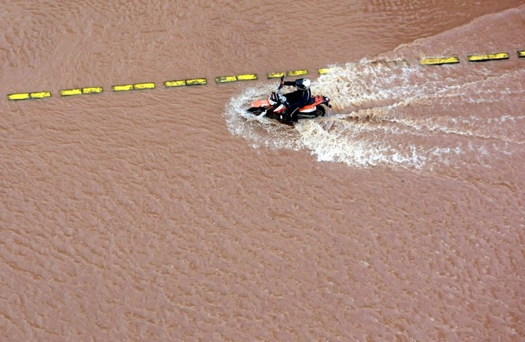An Indonesian motorbike rider travels through floodwater on a main road in Jakarta January 17, 2013 | © Bagus Indahono | EPA Photo