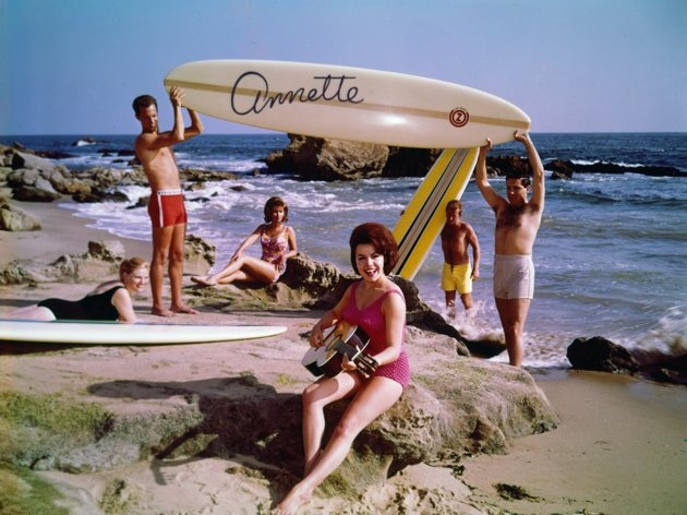 RIP Annette Funicello /  circa 1964:  EXCLUSIVE Promotional photo of American actor and singer Annette Funicello playing an acoustic guitar on the beach as two men hold up a surfboard with her name on it, for her album, 'Muscle Beach Party'. Other young women sit on the beach, wearing swimsuits.  (Photo by Gene Lester/Getty Images)