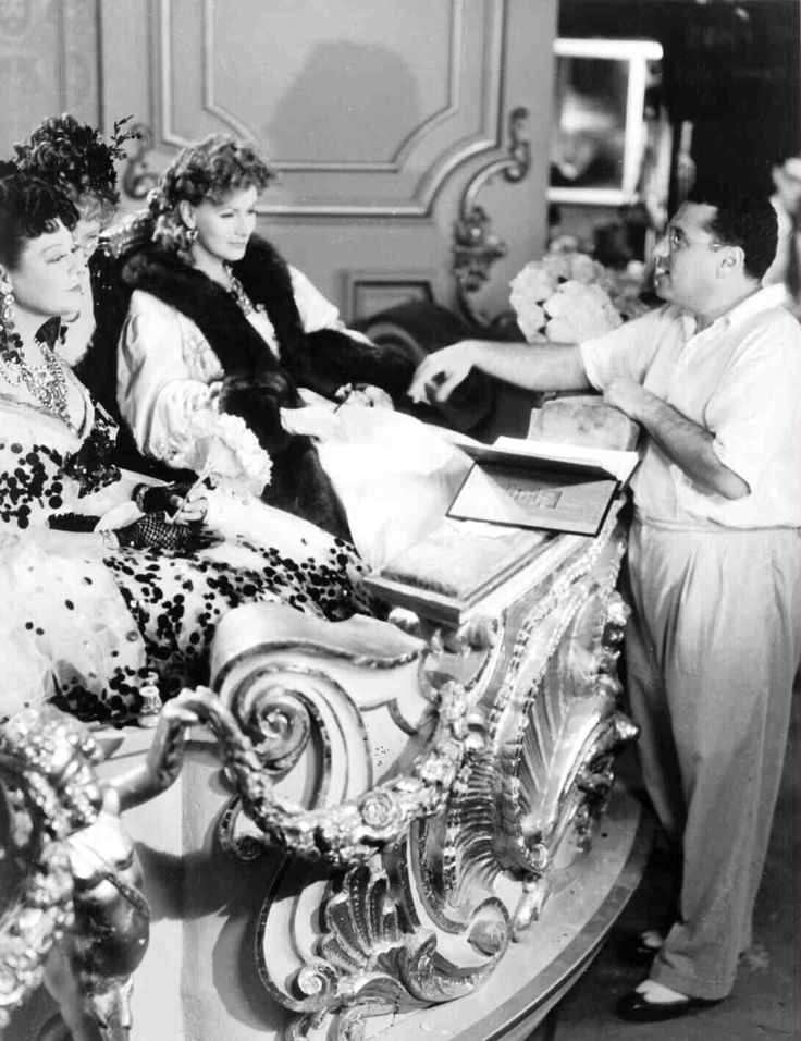 Full BTS shot of Lenore Ulric as Olympe, Greta Garbo as Marguerite Gautier (Camille), sitting in theater box set, and director George Cukor.