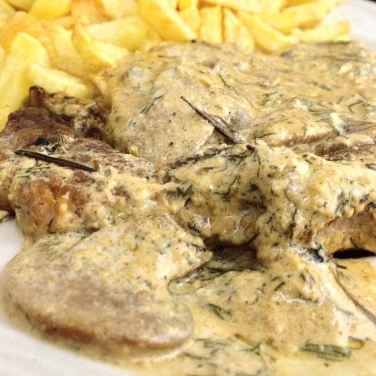 Baked pork steak with grilled mushrooms ala cream and rosemary