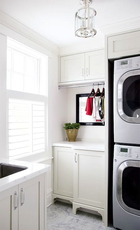 Style at Home - laundry/mud rooms - sleek laundry room, stacked washer and dryer, silver front-load washer and dryer, shaker cabinets, white shaker cabinets, utility sink, marble countertops, marble floor, laundry room lantern, lantern, laundry room cabinets, laundry room cabinet ideas,