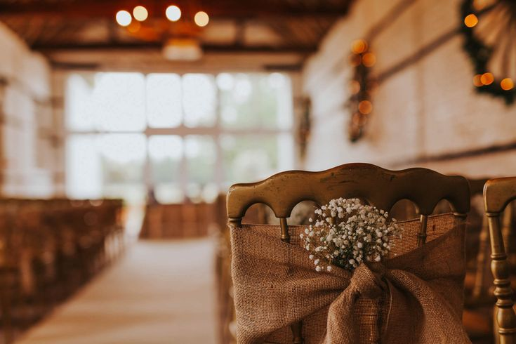 If you want to decorate your chairs, simple hessian and baby's breath on the aisle chair can help create impact. Photo by Benjamin Stuart Photography #weddingphotography #weddingdecor #weddingchairs #babysbreath #hessian #ceremonydecor #weddingday