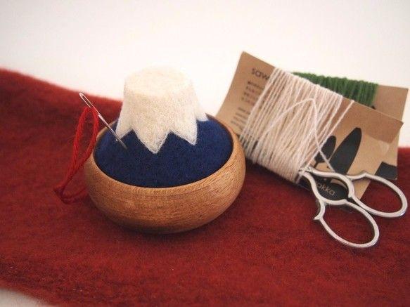 『 富士山の針山 』羊毛フェルトで、日本の富士山の針山(ピンクッション)を作りました。どこか温かみのある、木と羊毛の組み合わせ。お気に入りの道具になってもらえたら嬉しいです。富士山が好きな人へ外国の友人へのお土産へ手芸が好きな方へのプレゼントにもオススメです♪素材 :羊毛フェルト / 木〈ブナ〉サイズ :高さ5㎝位 横幅8㎝位 (木製器含む)ひとつひとつ手作業で制作していますので、又、天然の木の器の為、1つ1つ多少の違いがあります。ご理解の上お買い求めくださいませ。