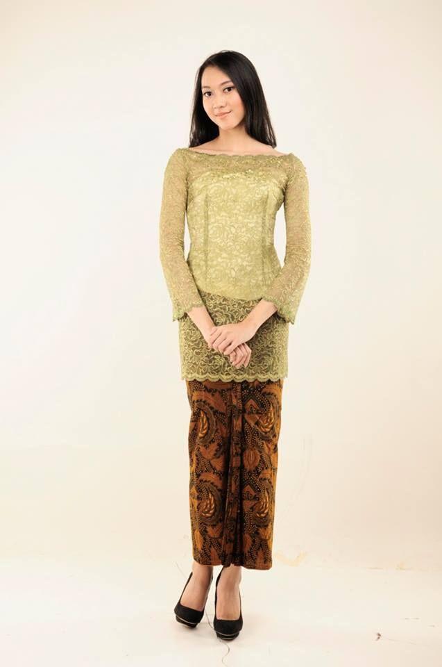 Kebaya sederhana berwarna hijau dengan kain batik tradisional.