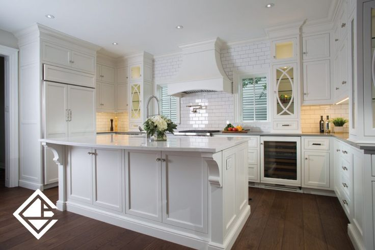 Dream white kitchen featuring white and concrete grey looking Caesarstone quartz countertops. The combination of white subway tiles, custom white range hood, and upper glass cabinets makes a beautiful classic kitchen design.