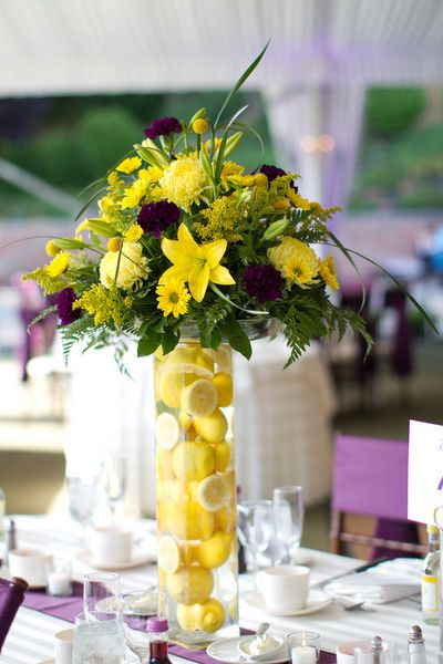Tall citrus centerpiece: cylinder vase filled with lemons (could do oranges or slices, too) and topped with matching yellow bouquet...floral design: teddi's flower shoppe catskill, ny