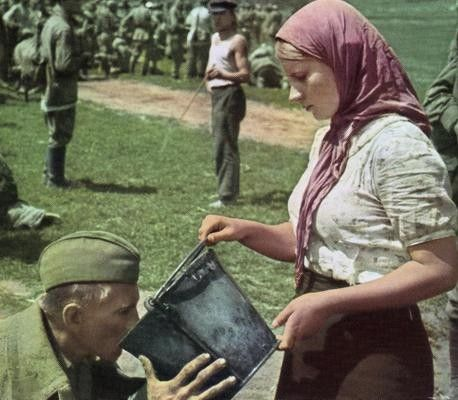 A UKRAINIAN woman gives water to a Soviet soldier after he has been captured, 1941.