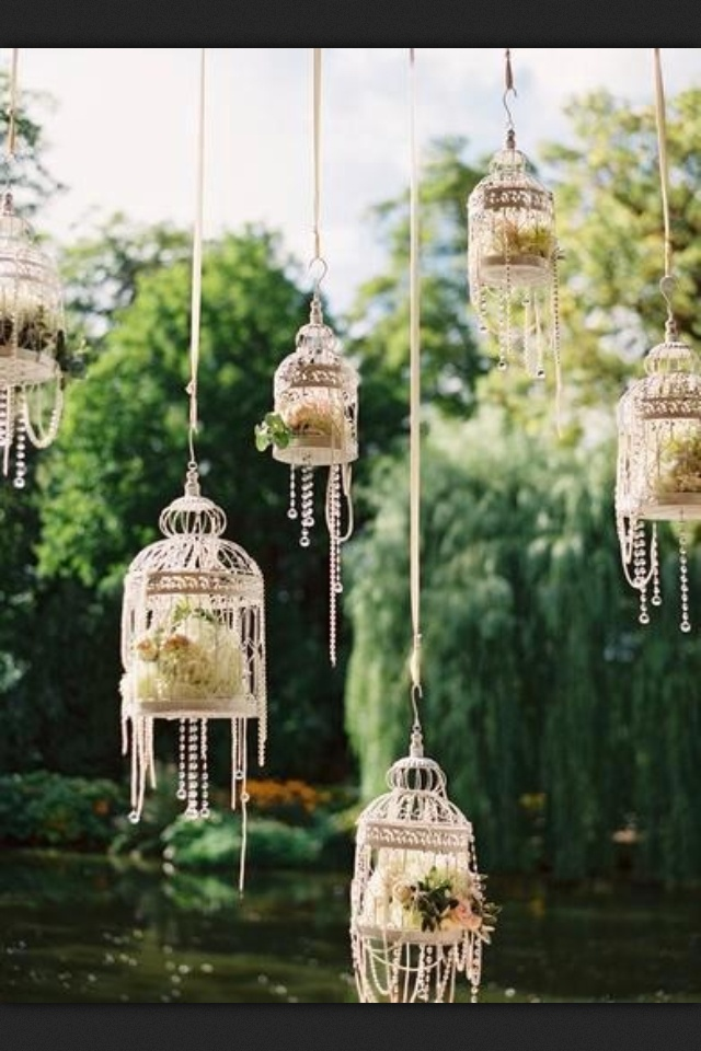 The pearl strands do more to romanticize these birdcages than the flowers contained within