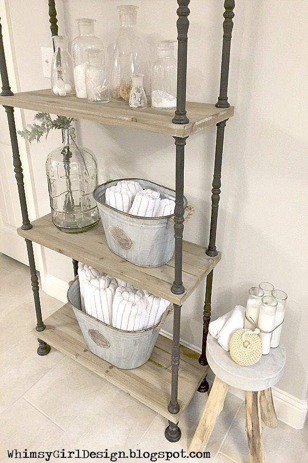 Galvanized buckets are the perfect solution to store and display bath towels on this rustic, wood shelf from HomeGoods. {Sponsored Pin}