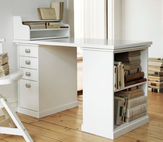 A white traditional desk with storage space showing vintage books. Klimpen Drawer unit and table leg with table top.