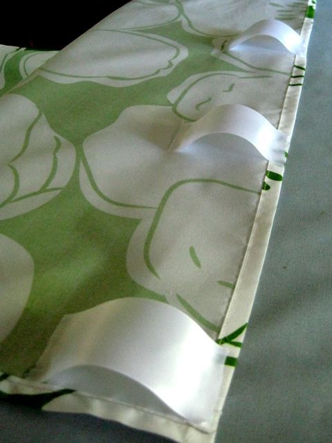 Hot glue ribbon tabs to turn a bed sheet into a no-sew curtain. brill.