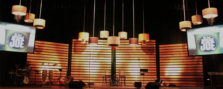 """Laura Blechle fromSouth Telegraph Christian Churchin St. Louis, MO brings us this coffee shop-vibed stage design. They grabbed some inspiration from Pining Away, building walls 1"""" x 6"""" x 10' from cedar decking boards. They attached the boards to the framework from the back and stood them by running wires up to the ceiling. Then they added faux barrel lights using fabric covered sono-tube. The lights did not actually have bulbs inside them. Instead, they were painted a soft creamy color…"""