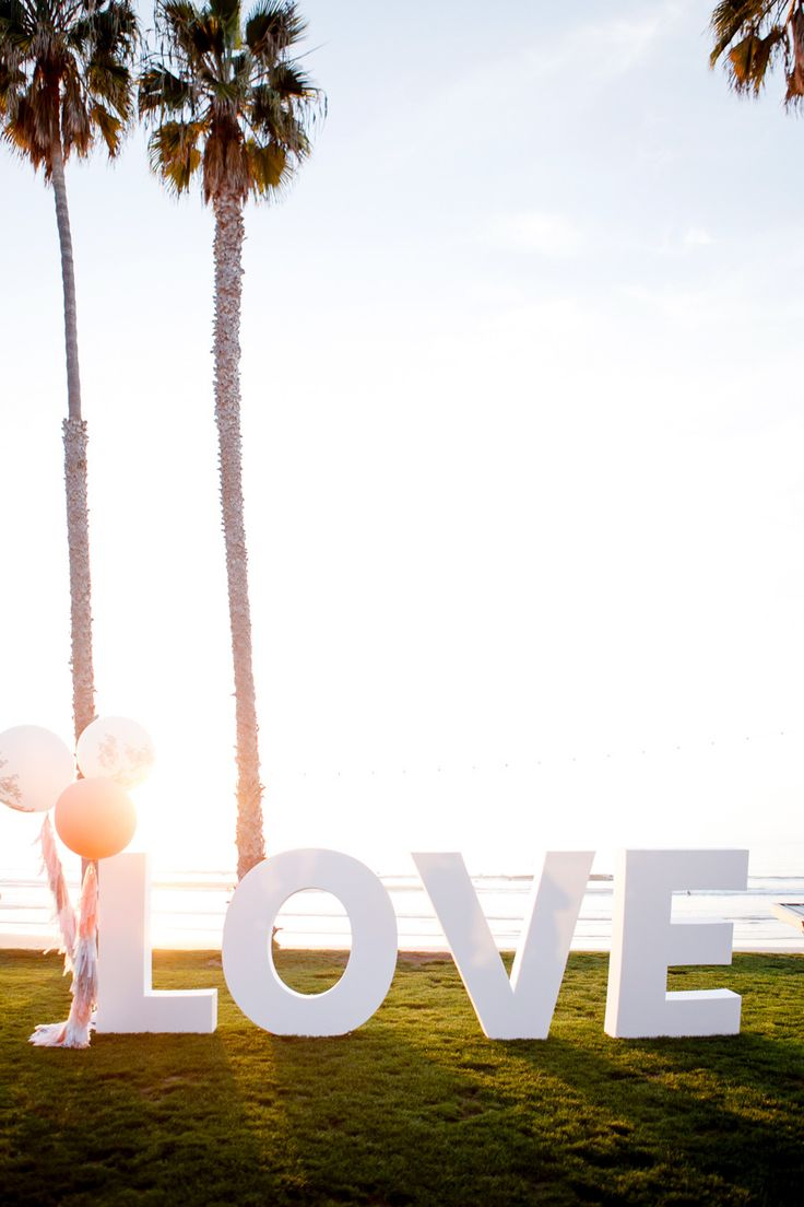 Giant LOVE Letters for fun -- See the wedding on #SMP here: http://www.StyleMePretty.com/2014/04/30/black-white-blush-seaside-wedding/ Photography: Ashlee Raubach Photography - www.ashleeraubach.com