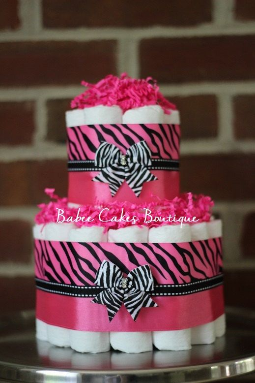 Mini 2 Tier Pink Zebra Diaper Cake    Cake Ingredients:  -27 Pampers size 1 diapers  -High quality ribbon  -Hot pink paper shred