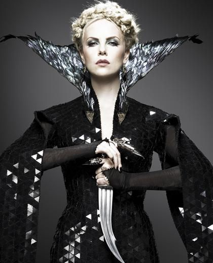 """Charlize Theron as the evil queen in """"Snow White and the Huntsman.""""  Love the way her dress has mirror bits, the feather collar, and her finger gauntlets."""