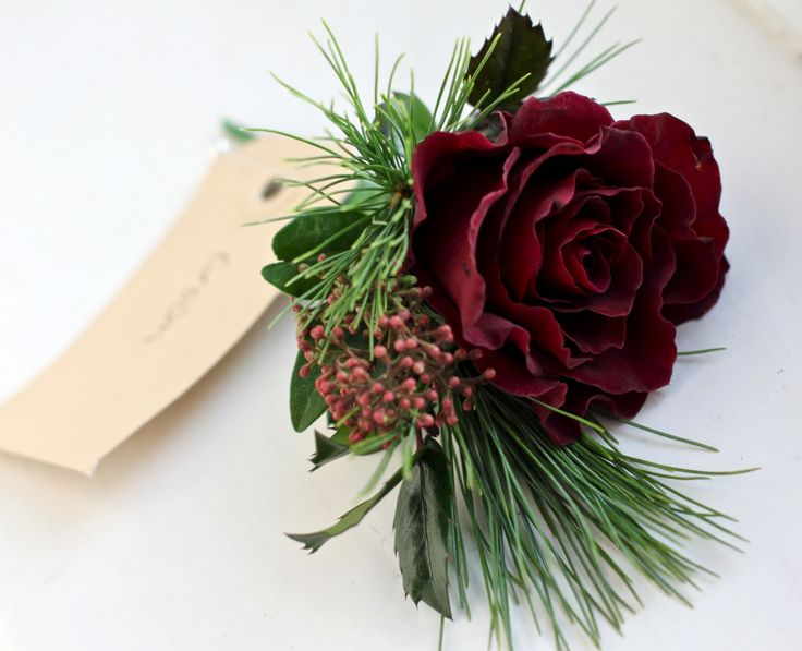 Winter wedding buttonhole with Christmas theme - burgundy rose, pine, holly and skimmia for the groom.
